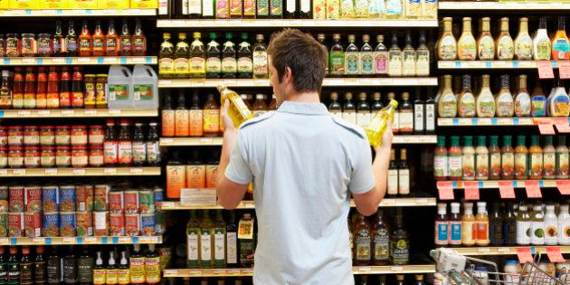 Young man in supermarket comparing bottles of oil, rear view,