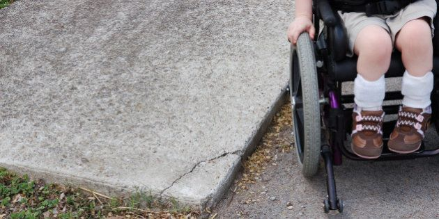 Young caucasion female child that is wheelchair bound with braces on her ankles that is trying to use...