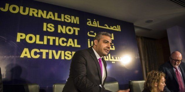 Egyptian-Canadian journalist Mohamed Fahmy, formerly with Al-Jazeera, is greeted by an unknown man duting...