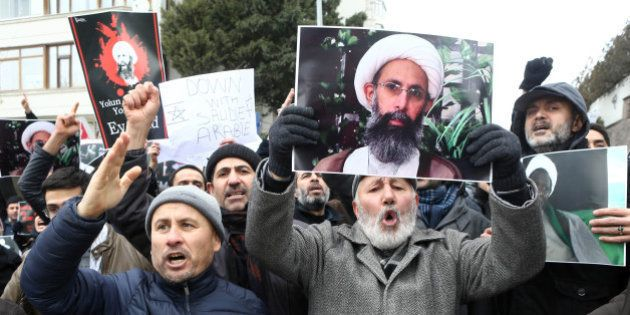 Iranian and Turkish demonstrators hold pictures of Shiite cleric Sheikh Nimr al-Nimr as they protest...