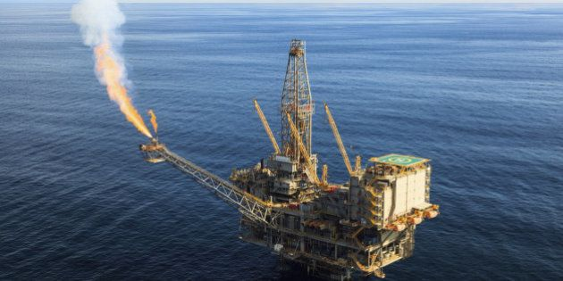Wide angle aerial photo of a massive oil rig in a calm, blue