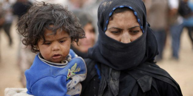 A Syrian refugee woman, who is stuck between the Jordanian and Syrian borders, holds her child as she...