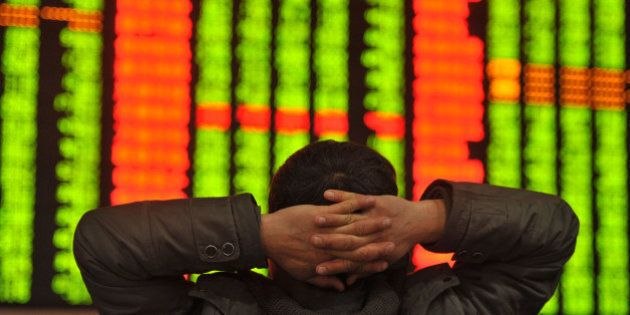 An investor sits in front of a screen showing stock market movements in a stock firm in Fuyang, east...