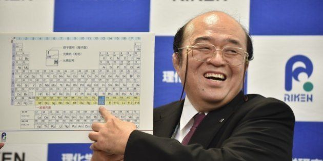 Kosuke Morita, the leader of the Riken team, smiles as he points to a board displaying the new atomic...