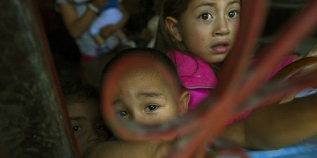 TOPSHOT - Childs displaced by the violence rest at their home during a visit of UN High Commissioner...