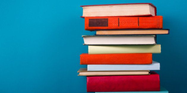 Stack of colorful books, grungy blue background, free copy space Vintage old hardback books on wooden...