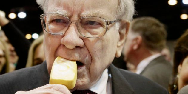 Berkshire Hathaway Chairman and CEO Warren Buffett eats an ice cream bar while touring the exhibition...