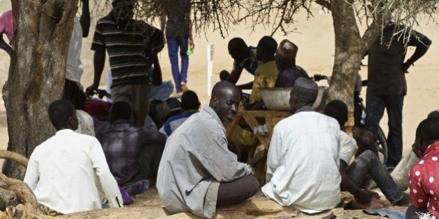 Nigerian refugees wait outside a tent of UNHCR, on April 7, 2015 in the Nigerian refugees camp named...