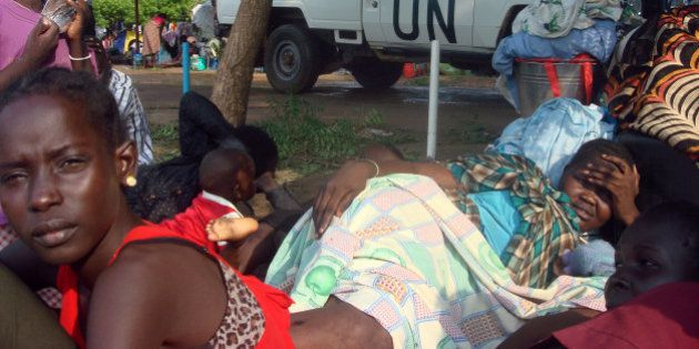 A U.N. truck drives past displaced South Sudanese families resting in a camp for internally displaced...