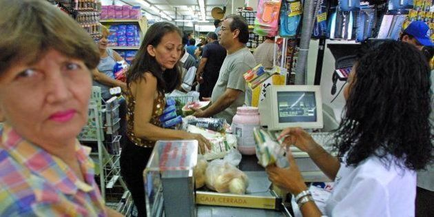 MARACAIBO, VENEZUELA: People make long lines to buy groceries at a supermarket in Maracaibo, 14 December...
