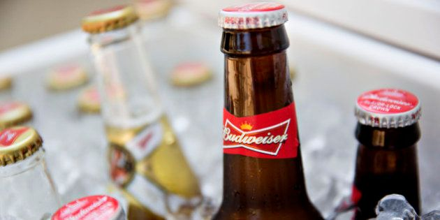 Bottles of Anheuser-Busch InBev NV Budweiser brand beer, right, are arranged for a photograph in a cooler...