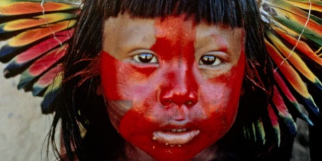 Kayapo boy with painted face and parrot-feather headdress; photographed in the Xingu Basin,