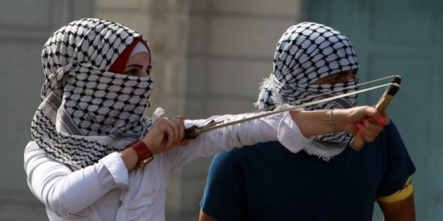 A Palestinian protester young woman uses a slingshot to throw stones during clashes with Israeli security...