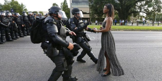 A demonstrator protesting the shooting death of Alton Sterling is detained by law enforcement near the...