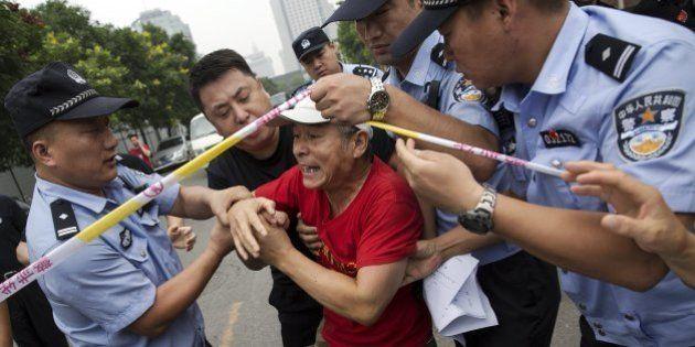 FOTOS: Parentes de vítimas do voo da Malaysia Airlines tentam invadir embaixada em