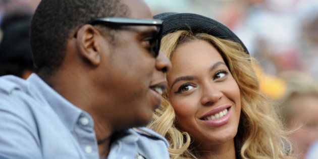 Entertainer Jay-Z (L) and wife Beyoncé (R) watch the men's final match between number one seed Novak...