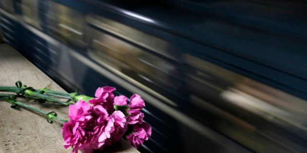 A train passes by flowers, left in memory of the victims of a bomb explosion, at Park Kultury metro station...