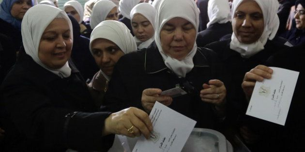Syrian women vote in the parliamentary elections at a polling station in Damascus on April 13, 2016.Polls...