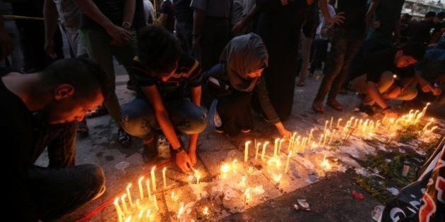 Iraqis light candles on July 9, 2016 at the site of a suicide-bombing attack which took place on July...