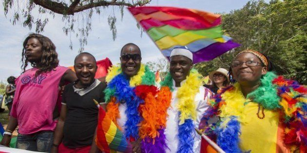People hold rainbow flags as they take part in the Gay Pride parade in Entebbe on August 8, 2015. Ugandan...