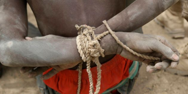 A prisoner, suspected of being a member of insurgent group Boko Haram, sits with his arms tied behind...