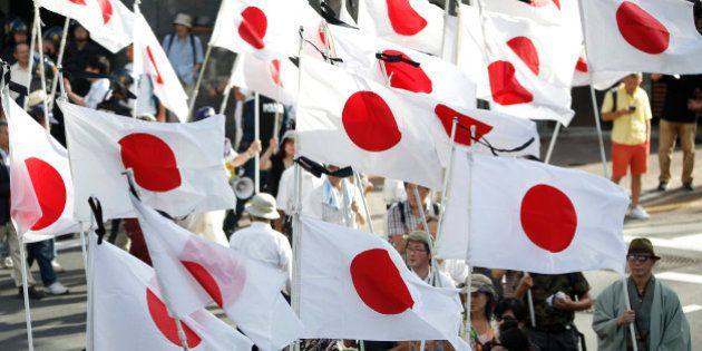 Demonstrators hold the Japanese national flag during a march near the Yasukuni Shrine in Tokyo, Japan,...