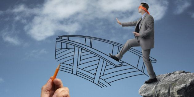 Businessman in a blindfold stepping off a cliff ledge with giant hand drawing a bridge for a safe crossing...