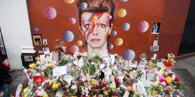 Floral tributes are seen beneath a mural of British singer David Bowie, painted by Australian street...