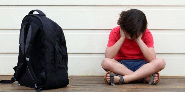 Sad student with school