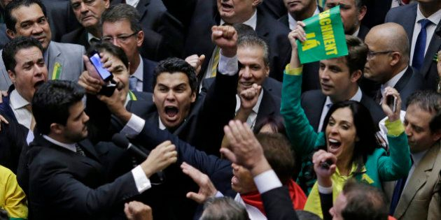 Members of the Lower House of Congress celebrate as they get close to enough votes in favor of the impeachment...