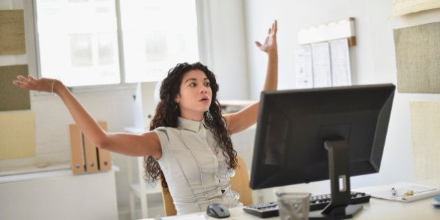 Mixed race businesswoman frustrated at computer at desk in