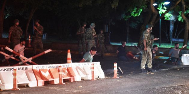Turkish security officers detain police officers on the side of the road on July 15, 2016 in Istanbul,...