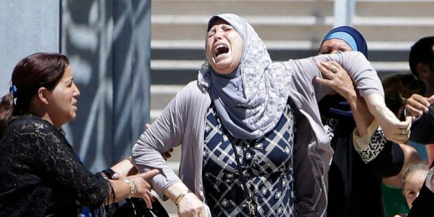 A woman reacts after learning of the death of a relative, outside the Pasteur hospital in Nice, southern...