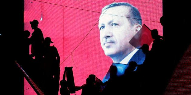 Turkish Supporters are silhouetted against a screen showing President Tayyip Erdogan during a pro-government...
