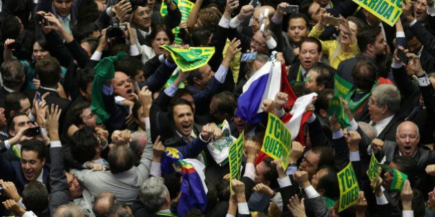 Opposition lawmakers celebrate after the lower house of Congress voted to impeach Brazil's President...