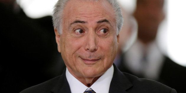 Brazil's interim President Michel Temer reacts during a presentation ceremony of the Delegation of the...