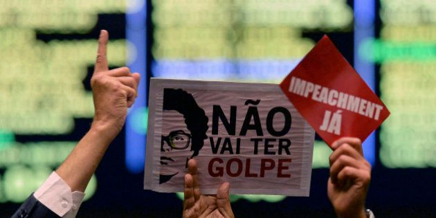 Brazilian congressmen show signs against (R) and supporting (L) Brazilian President Dilma Rousseff during...