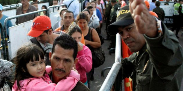 A Colombian police officer gives direction to people lining up to cross over the Simon Bolivar international...