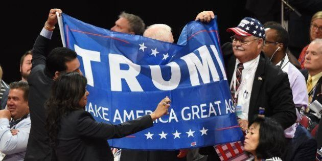 A delegate takes a selfie in front of a banner in support of Republican presidential candidate Donald...