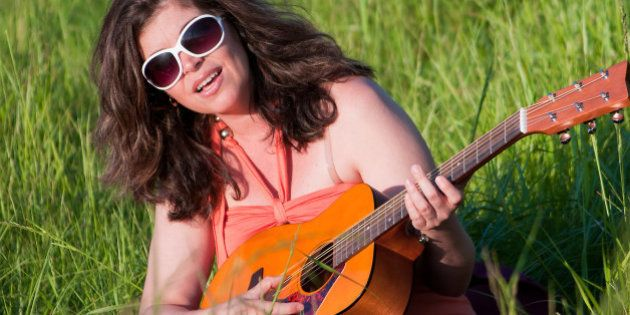 TORONTO, ONTARIO, CANADA - 2011/06/05: Woman playing accoustic guitar with long hair in sunglasses sitting...
