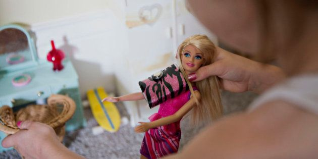 A young girl plays with a Mattel Inc. Barbie doll in Tiskilwa, Illinois, U.S., on Wednesday, July 1,...