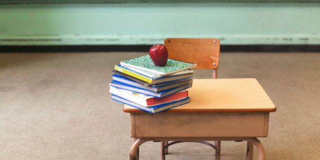 Stack of school books and apple on desk in empty