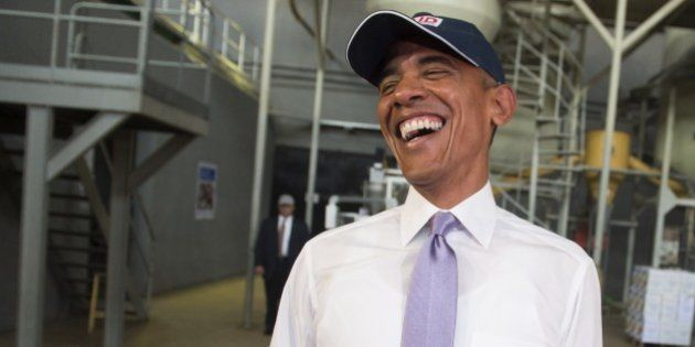 US President Barack Obama laughs as he looks at members of the press wearing hairnets during a tour of...