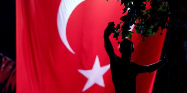 A supporter of Turkish President Tayyip Erdogan takes a selfie in front of a giant Turkish national flag...