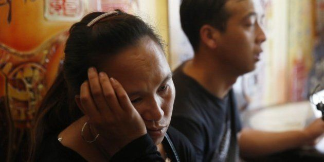 A family member (L) of missing firefighters mourns after being barred from a press conference in Tianjin...
