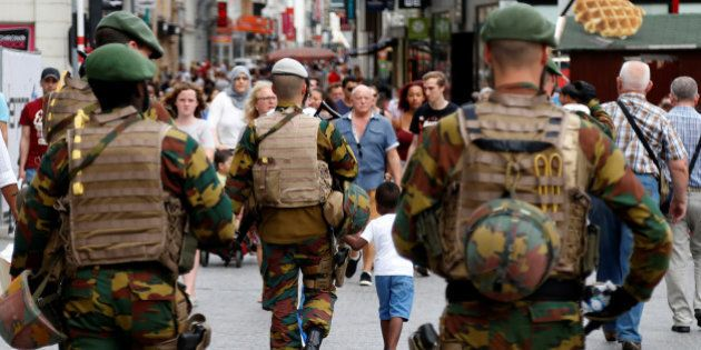 Belgian soldiers patrol on a square after a man was seen wearing a thick coat with wires protruding from...