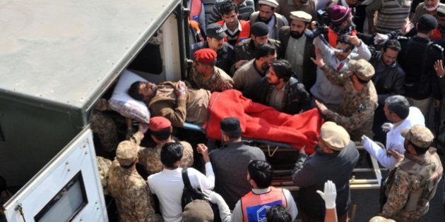 Pakistani rescuers shift an injured victim in an army ambulance from a hospital following an attack by...