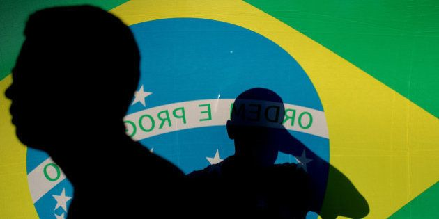 Anti-government demonstrators walk past a Brazilian flag during a demonstration in favor of the impeachment...