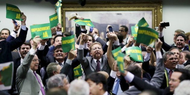 Members of the impeachment committee react after voting on the impeachment of Brazilian President Dilma...