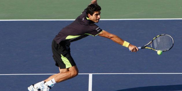 SHANGHAI, CHINA - OCTOBER 17: Marcelo Melo of Brazil returns a shot against Rohan Bopanna of India and...